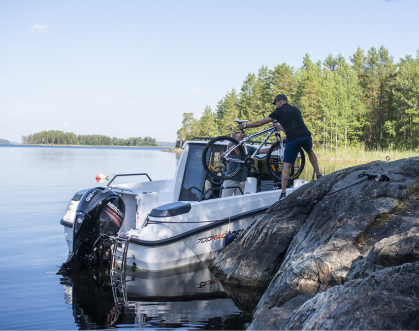 Man taking a mountain bike out of Bella boat.